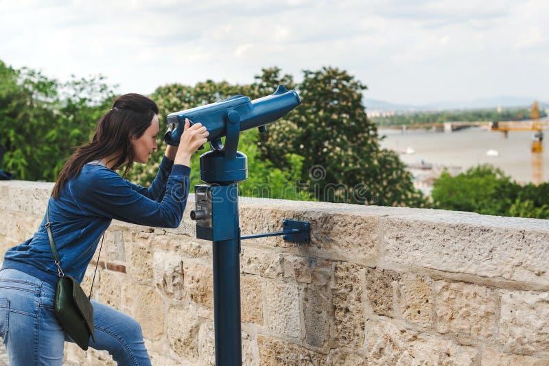 Mulher do turista do curso em feriados de Europa A menina do moderno que usa o telescópio olha o panorama da cidade Viagem, laze fotos de stock royalty free