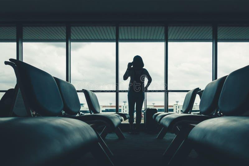 A mulher do turista da silhueta falar no telefone celular quando standi fotografia de stock