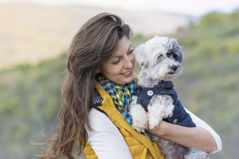 Mulher do turista que abraça seu cão de caniche branco exterior foto de stock