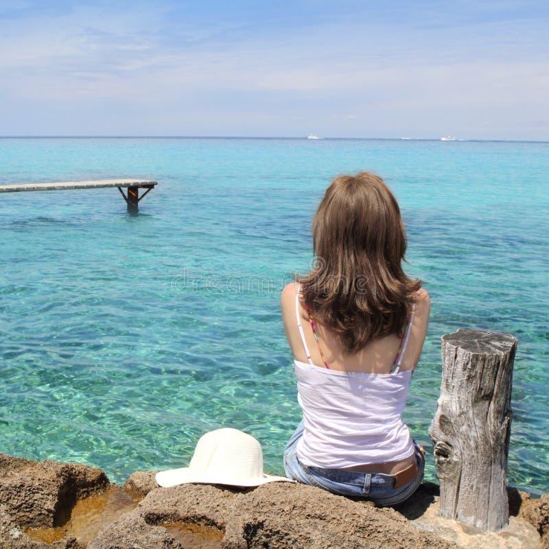 Mulher do turista que olha o mar de turquesa de Formentera fotos de stock