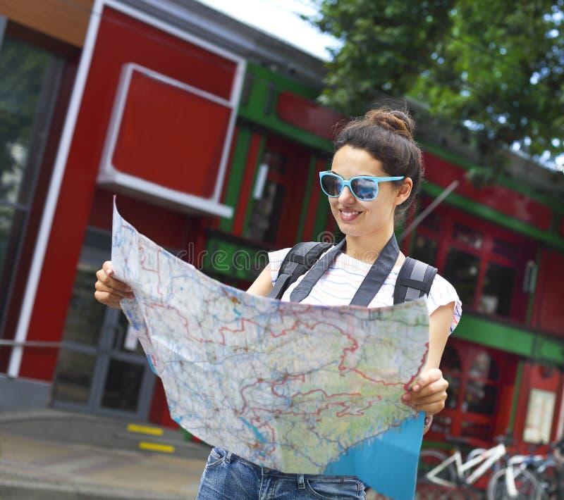 Mulher do turista que procura o sentido no mapa de lugar fotografia de stock