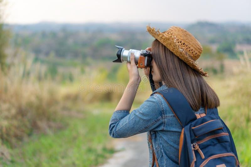 Mulher do turista que toma a foto com sua câmera na natureza imagem de stock royalty free