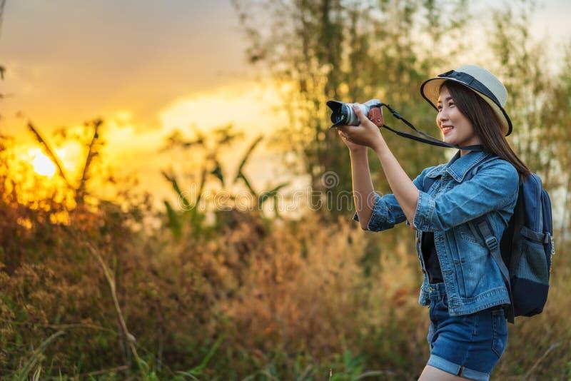 Mulher do turista que toma uma foto com a câmera na natureza com por do sol imagens de stock royalty free