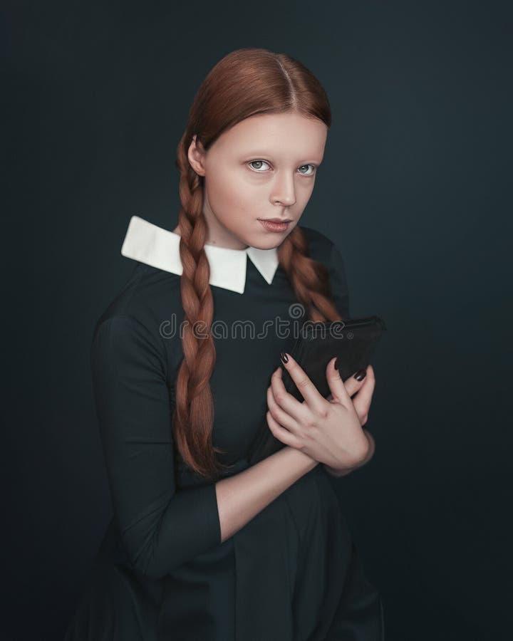 A mulher do vampiro de Dia das Bruxas olha diretamente na câmera que guarda o livro Retrato fêmea no estilo do vintage no fundo e foto de stock