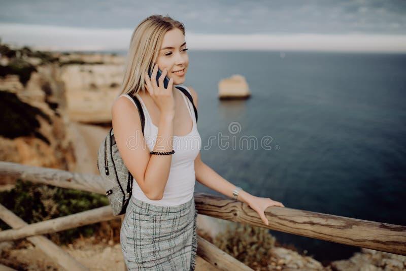 Mulher do verão que usa a mensagem texting dos sms do telefone celular fora Moça feliz de Europa que relaxa no sol no telefone ce imagens de stock royalty free