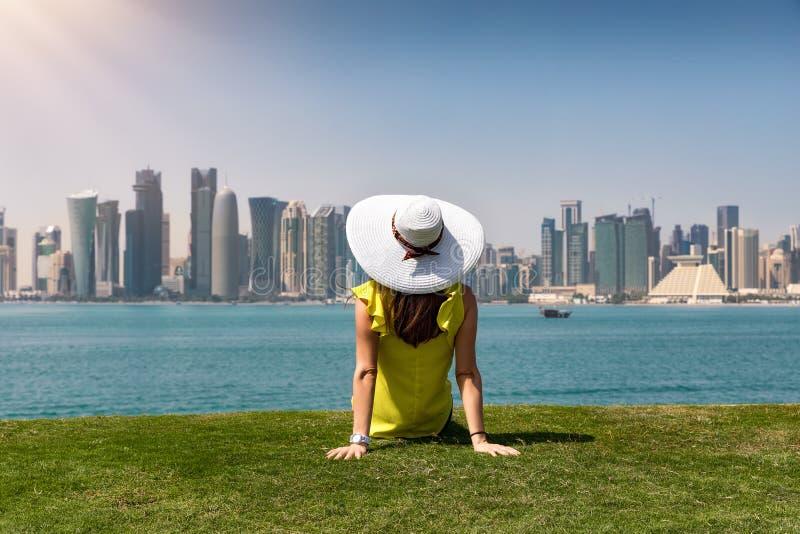 A mulher do viajante aprecia a vista à skyline de Doha, Catar imagens de stock