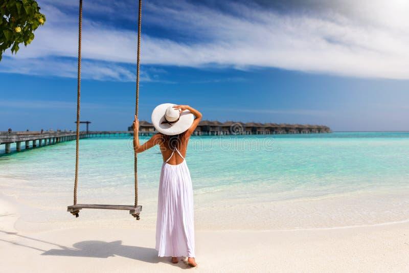 A mulher do viajante está próximo a um balanço em uma praia tropical fotos de stock royalty free