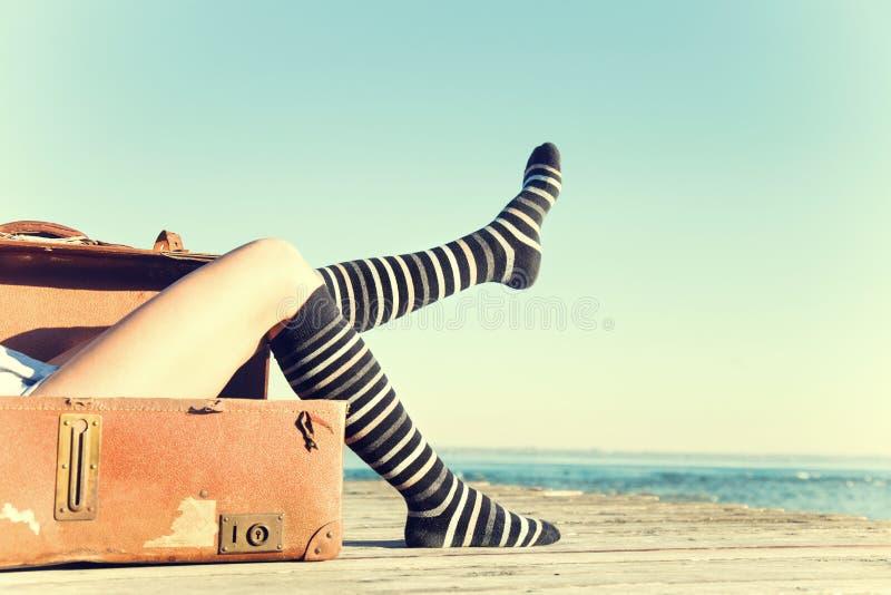 A mulher do viajante move seus pés que sentam-se em sua mala de viagem foto de stock