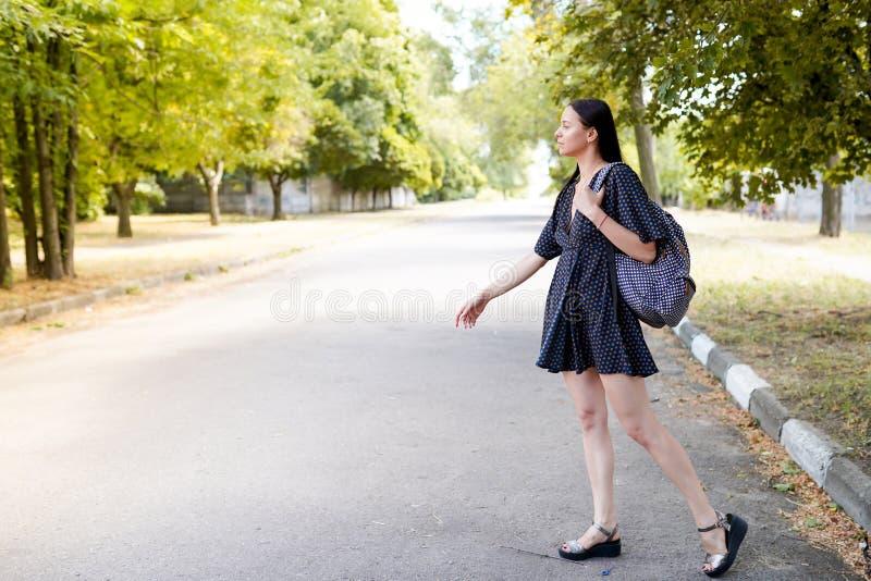 A mulher do viajante olha afastado na estrada menina no vestido e saco, fundo da natureza com espaço da cópia foto de stock royalty free
