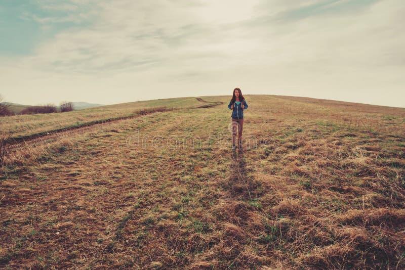 Mulher do viajante que anda no prado fotografia de stock