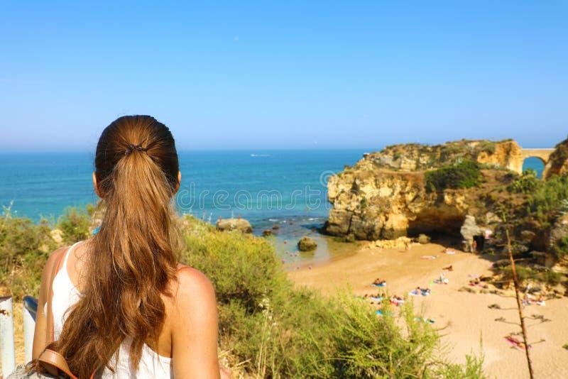 Mulher do viajante que aprecia e que relaxa a vista impressionante de Portugal do sul Opinião traseira a menina bonita em seu cur imagem de stock royalty free