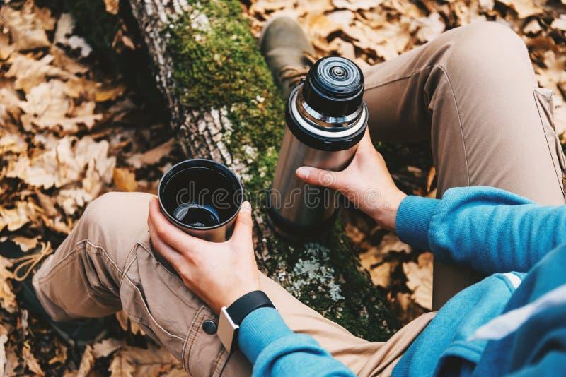 Mulher do viajante que guarda um copo do chá e a garrafa térmica na floresta do outono imagens de stock royalty free