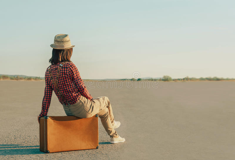 Mulher do viajante que senta-se na mala de viagem na estrada, cópia-espaço fotos de stock royalty free