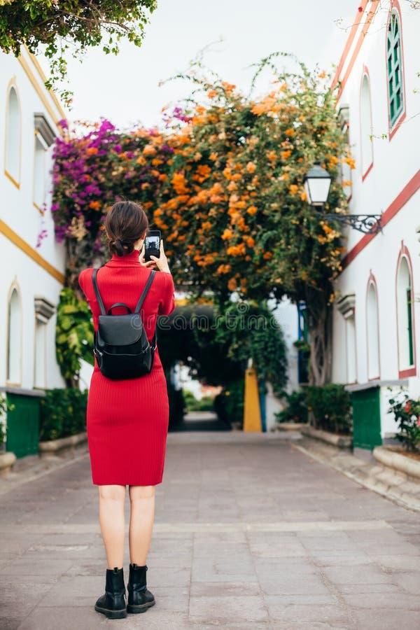 Mulher do viajante que toma uma foto da rua com flores usando mobil fotos de stock