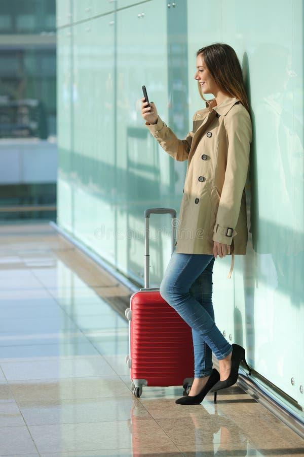 Mulher do viajante que usa um telefone esperto e esperando em um aeroporto imagem de stock
