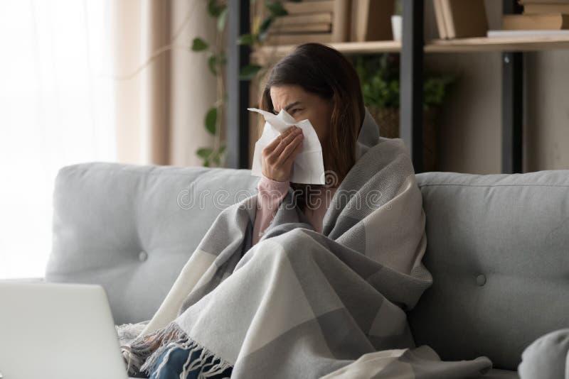 Mulher doente coberta com o nariz de sopro da manta no tecido do papel fotos de stock