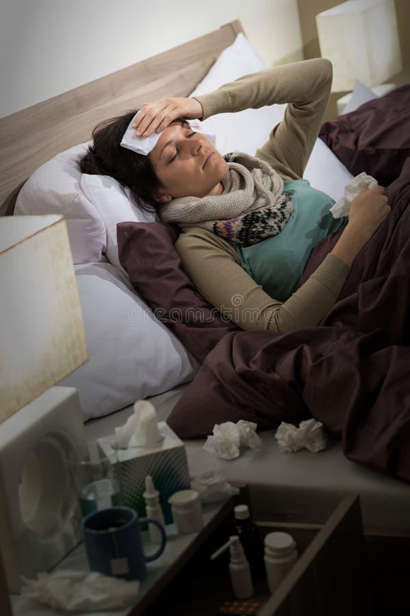 Mulher doente com a gripe que encontra-se na cama imagem de stock