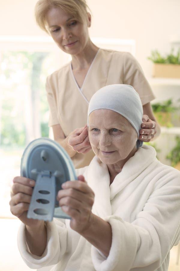 Mulher doente com um lenço do cabelo que olha si mesma no espelho Enfermeira que está no fundo imagem de stock royalty free