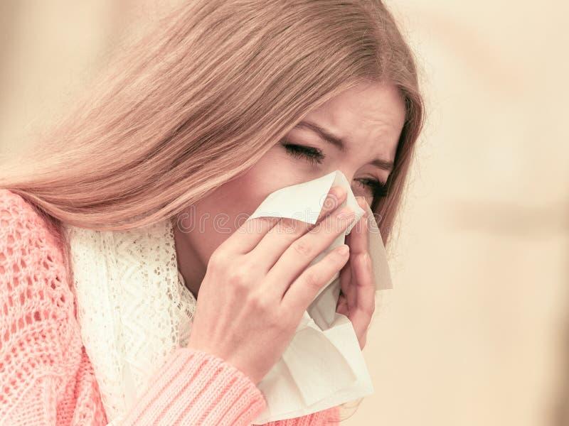 Mulher doente doente no parque do outono que espirra no tecido fotografia de stock royalty free