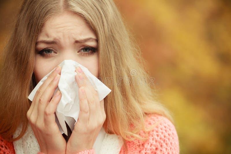 Mulher doente doente no parque do outono que espirra no tecido fotos de stock royalty free