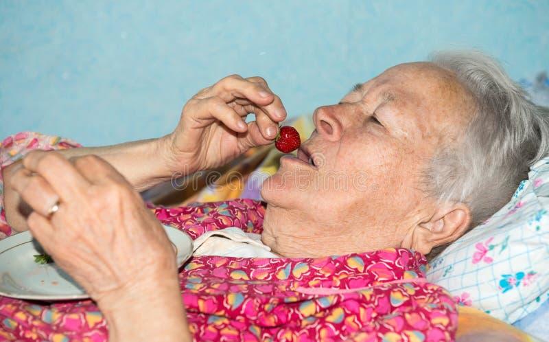 Mulher doente idosa que come a morango imagem de stock