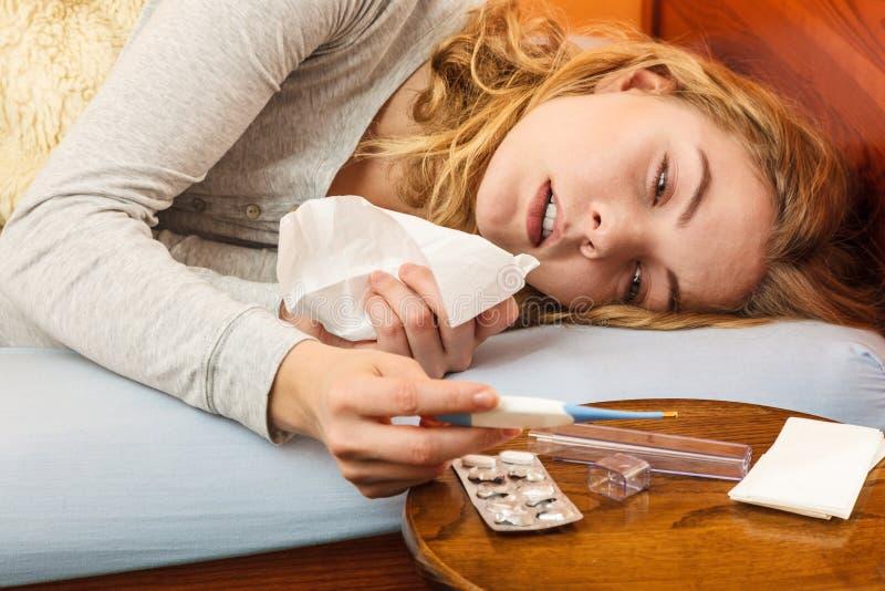 Mulher doente na cama com tecido e termômetro imagens de stock royalty free