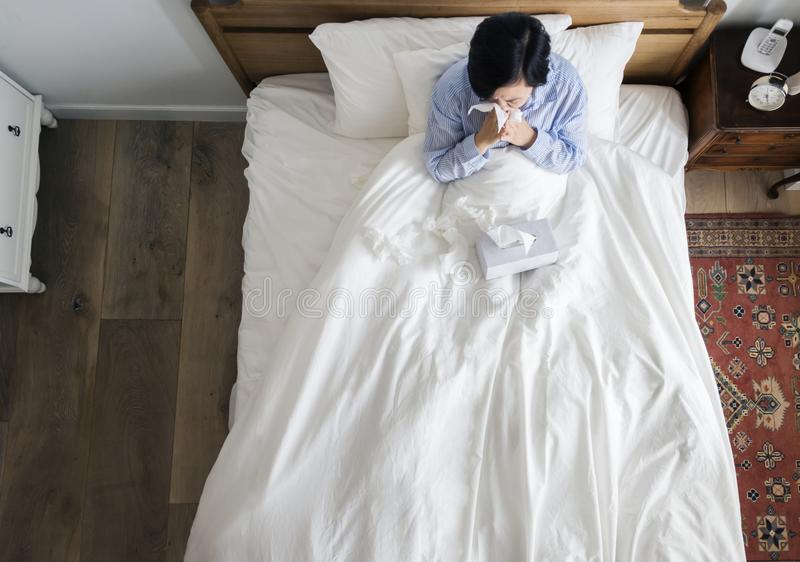 Mulher doente na cama que funde seu nariz foto de stock royalty free