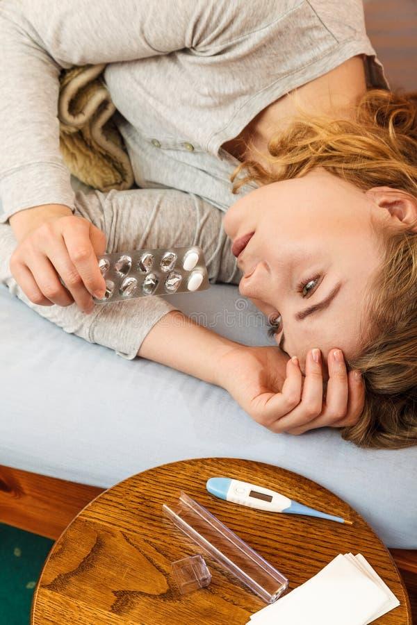 Mulher doente na cama que toma comprimidos Tratamento da saúde foto de stock