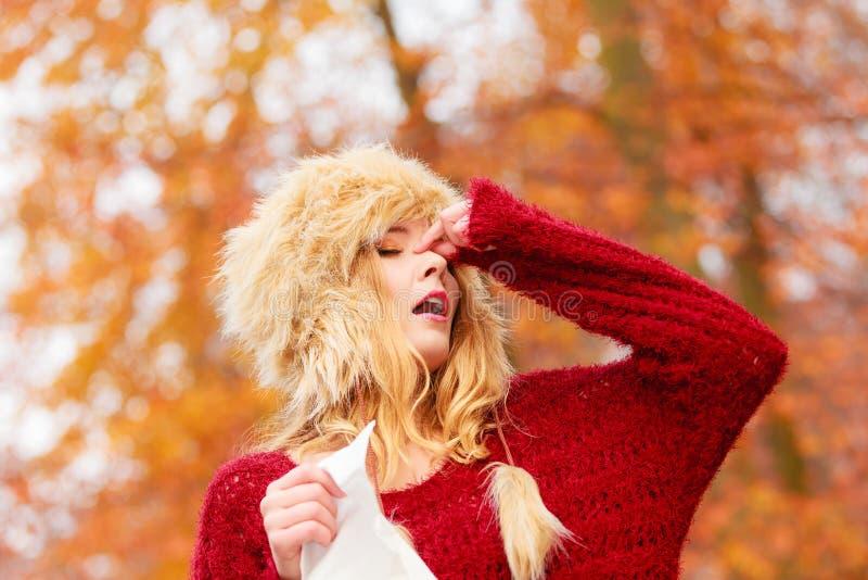 Mulher doente no parque do outono que espirra no tecido fotografia de stock