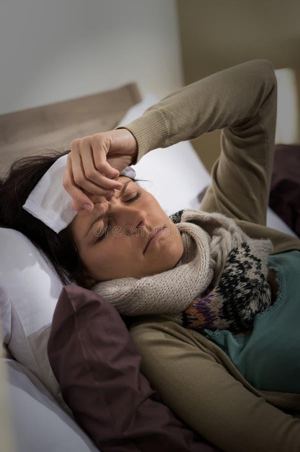 Mulher doente nova que está com a gripe da febre alta foto de stock royalty free