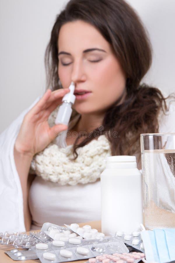 Mulher doente nova que usa o pulverizador nasal em sua sala de visitas fotografia de stock