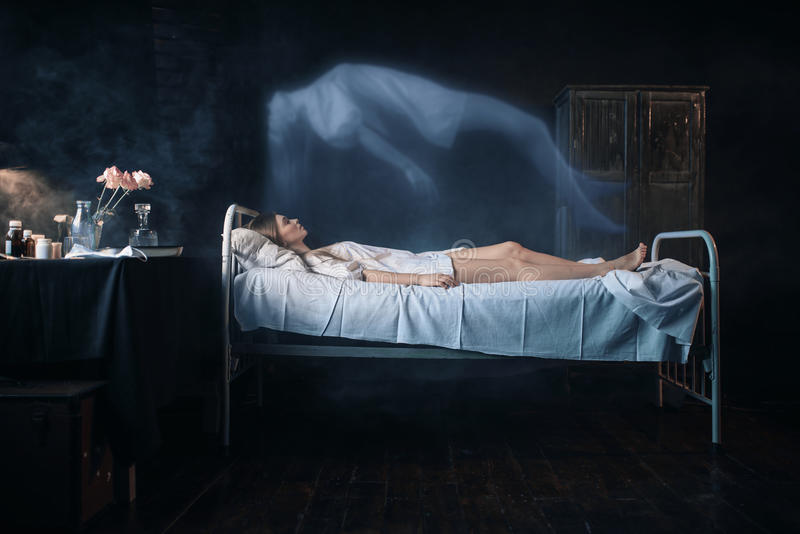 A mulher doente que encontra-se na cama de hospital, alma deixa o corpo fotos de stock royalty free