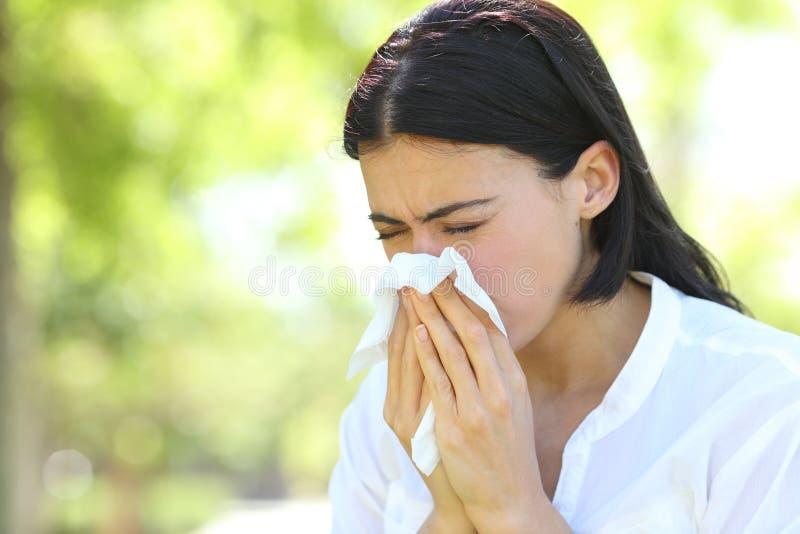 Mulher doente que espirra cobrindo a boca com uma limpeza em um parque foto de stock royalty free