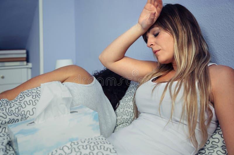Mulher doente que espirra e que cobre o nariz com o tecido fotos de stock