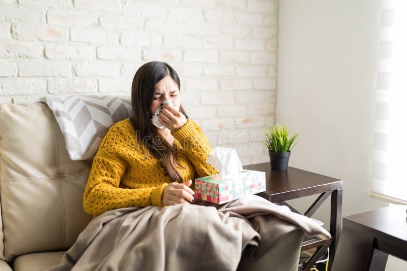 Mulher doente que espirra em casa fotos de stock