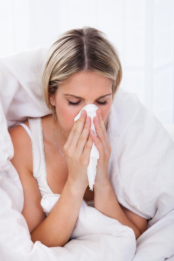 Mulher doente que funde seu nariz imagem de stock