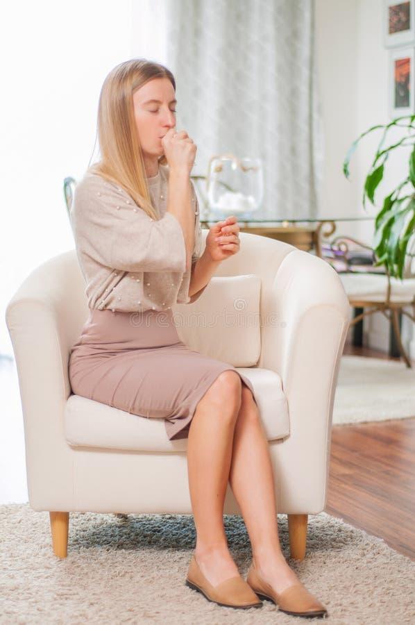 Mulher doente que tem a tosse e o frio em casa imagens de stock