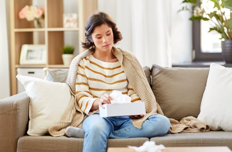 Mulher doente que toma o tecido de papel da caixa em casa fotos de stock royalty free