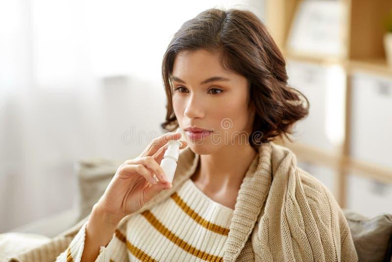 Mulher doente que usa o pulverizador nasal em casa imagens de stock