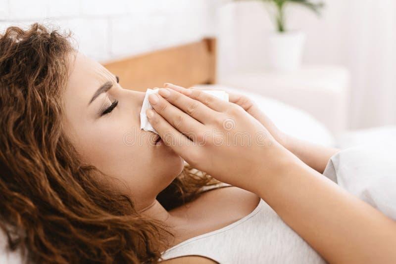 A mulher doente tem o nariz ralo em casa fotos de stock royalty free