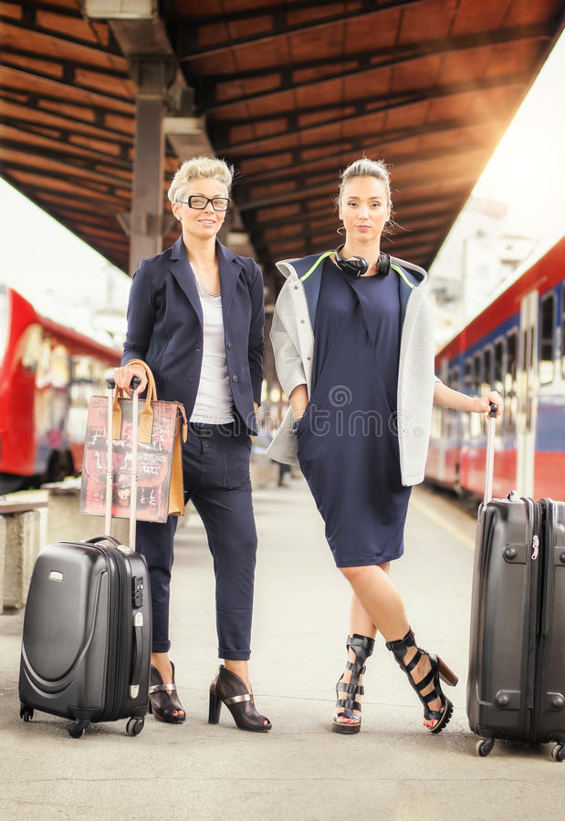 Mulher dois elegante com a mala de viagem que levanta na estação de trem imagem de stock