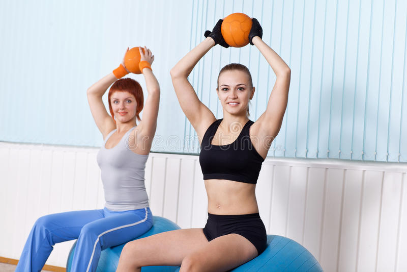 A mulher dois faz exercícios com esfera dura imagens de stock