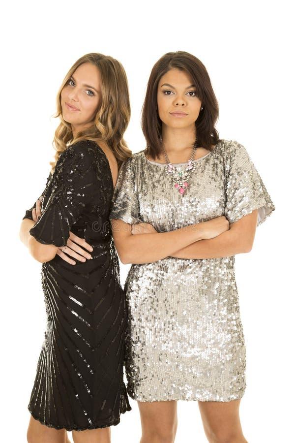 Mulher dois nos braços brilhantes do suporte dos vestidos dobrados imagem de stock