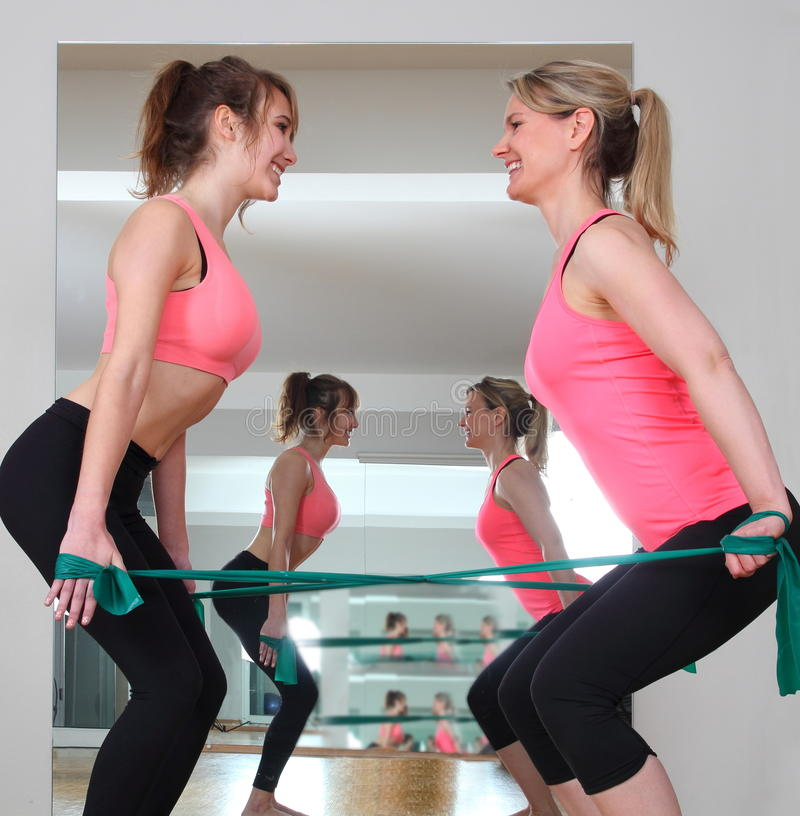 Mulher dois que faz o exercício com faixas da aptidão imagem de stock royalty free