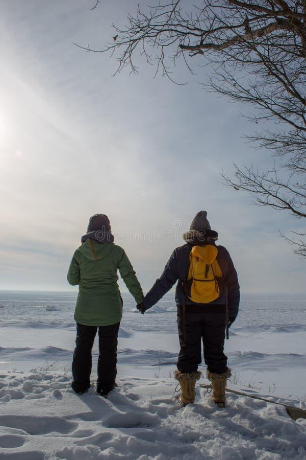 Mulher dois que guarda as mãos com as partes traseiras giradas na costa congelada p do lago imagem de stock royalty free