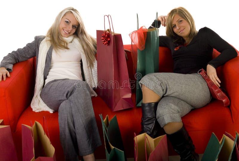 Mulher dois que senta-se entre sacos de compra fotos de stock royalty free