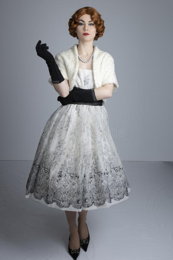 mulher dos anos 50 no vestido preto e branco que veste uma estola de pele fotografia de stock