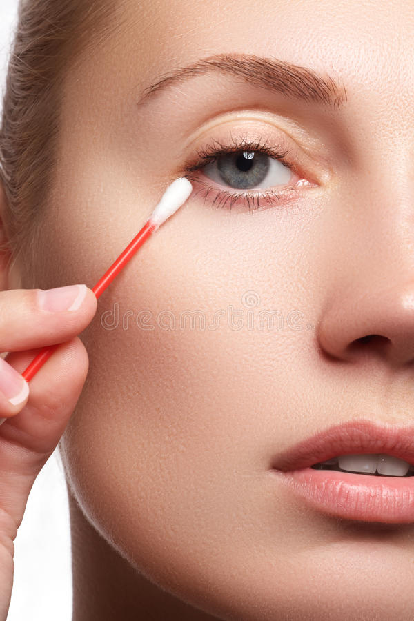 Mulher dos cuidados com a pele que remove a composição da cara com o cotonete de algodão Conceito do cuidado de pele Modelo cauca imagens de stock