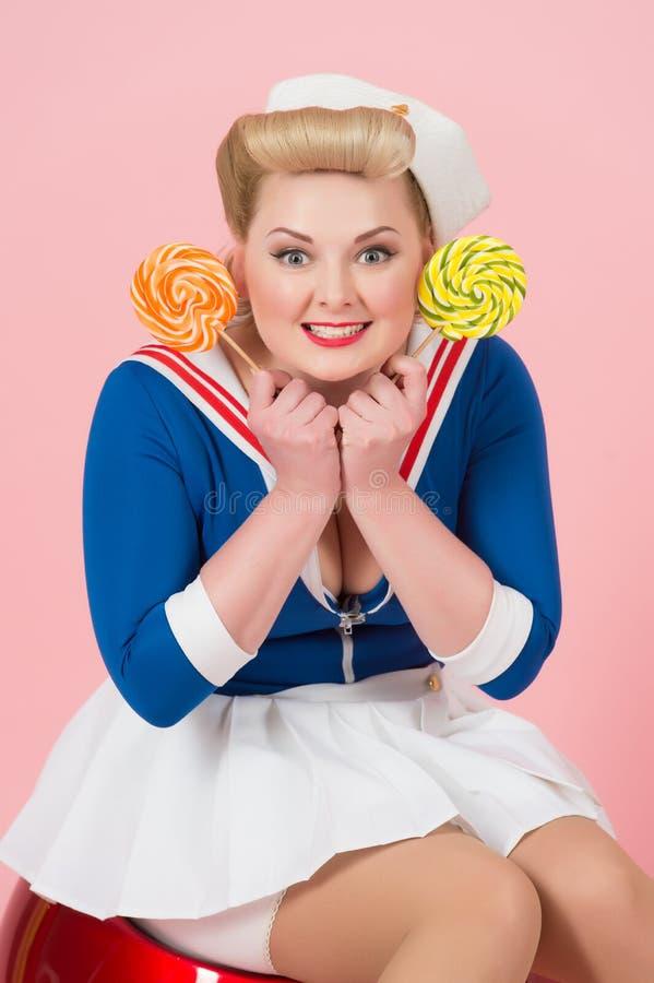 Mulher dos doces no estilo retro do pino-acima Menina loura com os doces nas mãos Mulher feliz bonita com os pirulitos isolados n imagens de stock