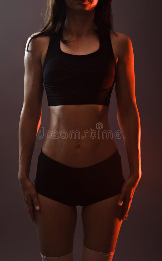 Mulher dos esportes na parte superior preta e short em um fundo cinzento imagem de stock royalty free